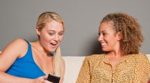 Friends looking at cell phone - women smartphone