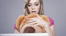 Teenage girl with soft toy looking shockly at laptop - fear woman laptop