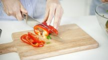 A woman cutting a paprika - kitchen cooking tomato