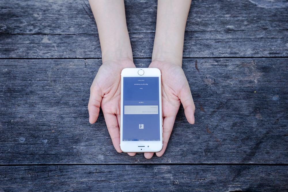iPhone z włączonym Facebookiem na dłoniach
