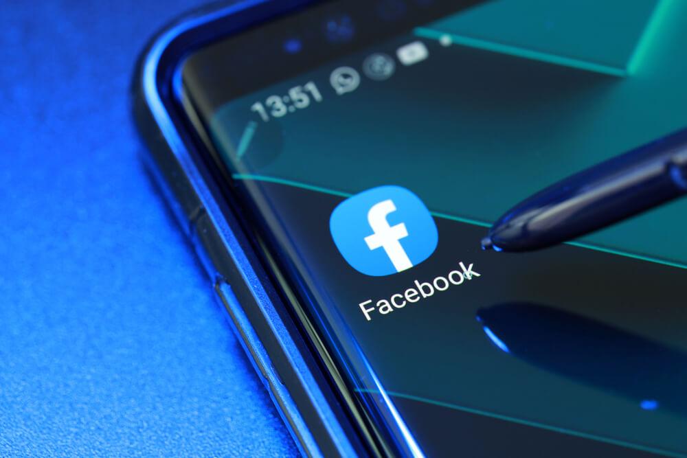 logo aplikacji Facebook na pulpicie telefonu. Telefon leży na niebieskim tle