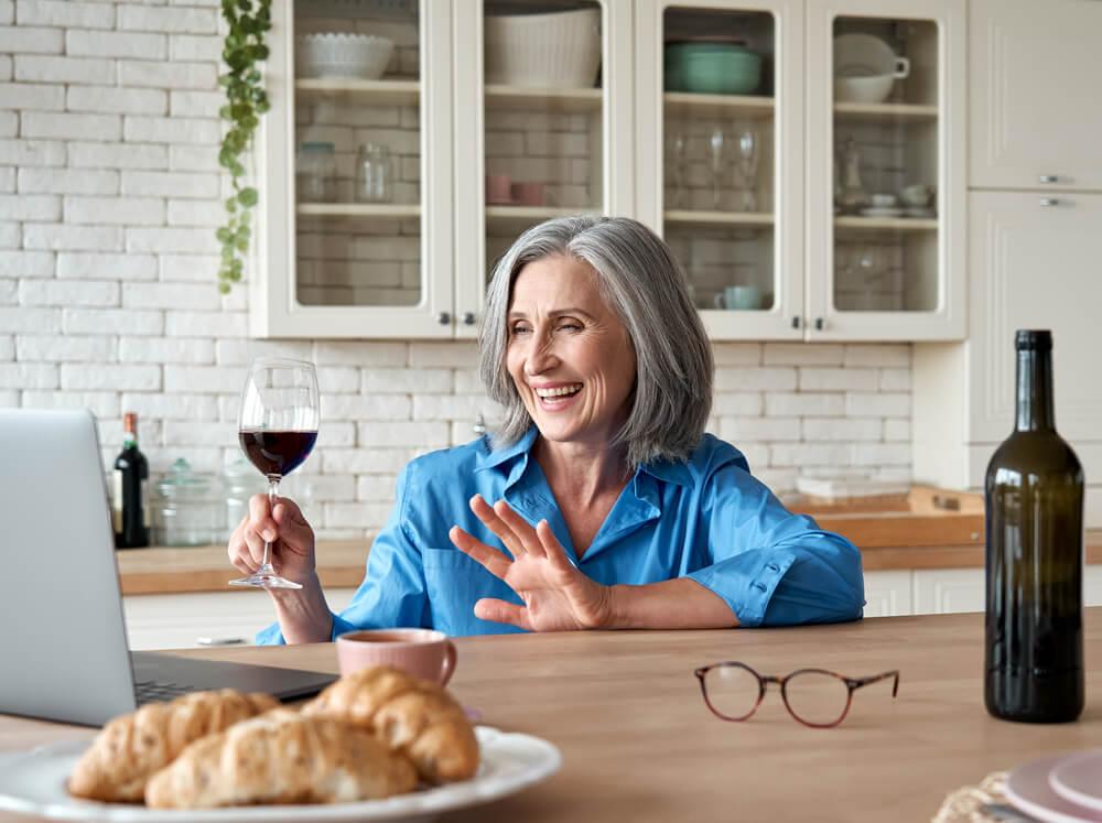 starsza pani z winem, machająca do osoby, z którą rozmawia na laptopie