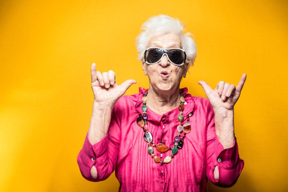 wyluzowana starsza kobieta w różowej bluzce i koralach