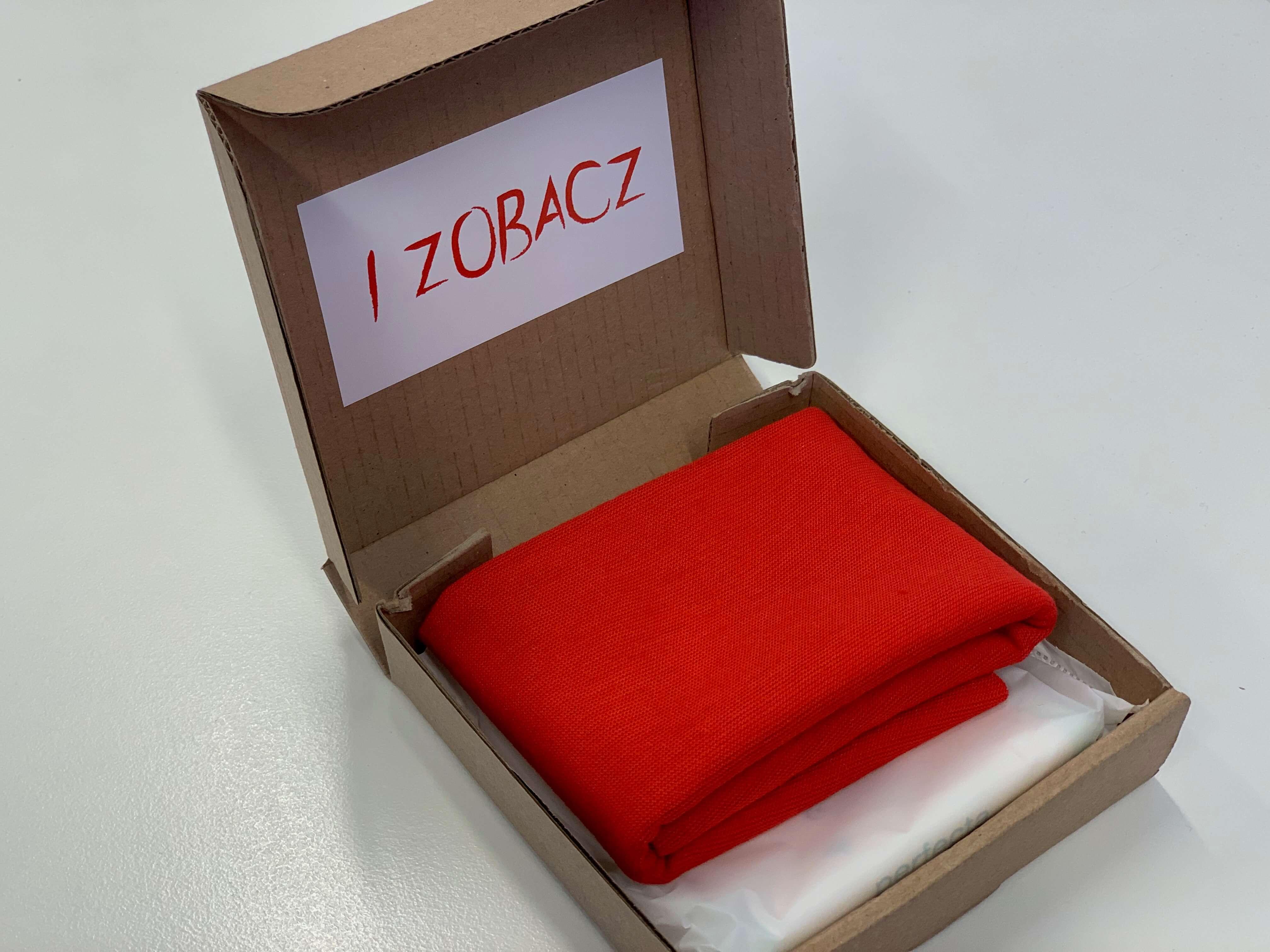 """Otwarte tekturowe pudełko, z napisem """"I zobacz"""" na wieczku i czerwoną opaską w środku."""