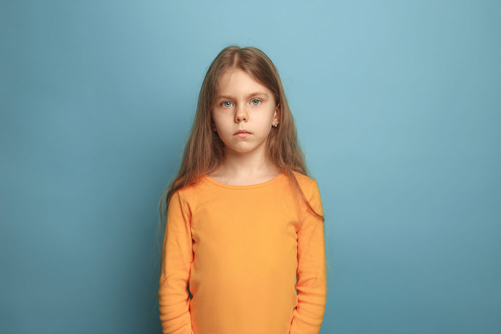 Smutna dziewczynka, w żółtej bluzce na długi rękaw. Stoi na tle szarej ściany.