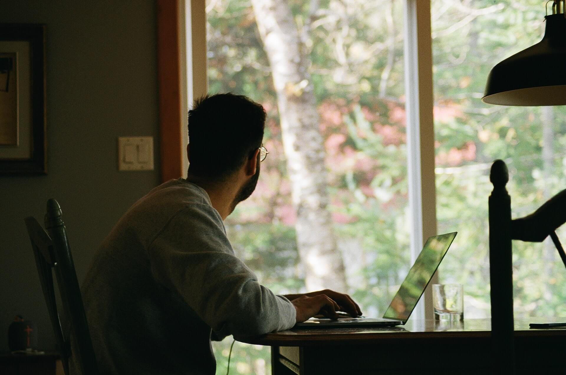 mężczyzna patrzący w okno na home office