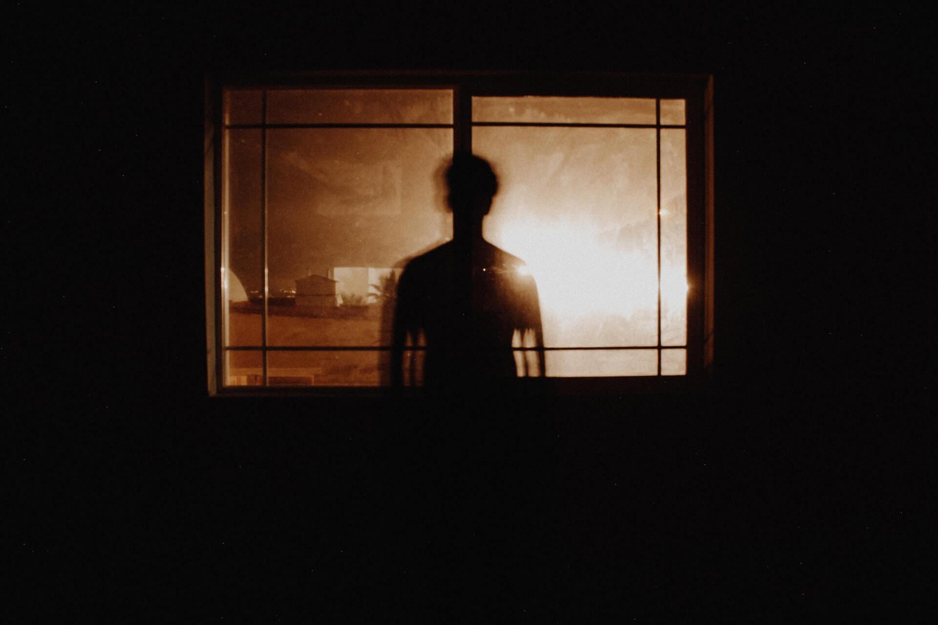 Kontur człowieka stojącego w oknie. Zdjęcie zrobione w sepii.
