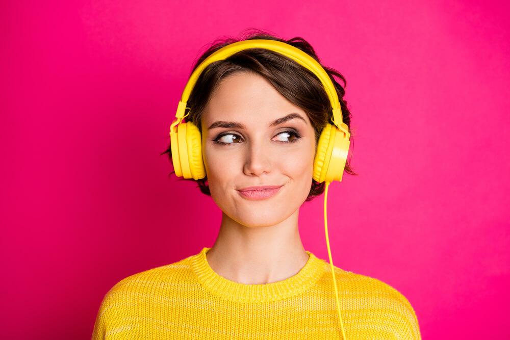 Kobieta w źółtym sweterku, z założonymi żółtymi słuchawkami, na ciemno różowym tle. Jest uśmiechnięta.