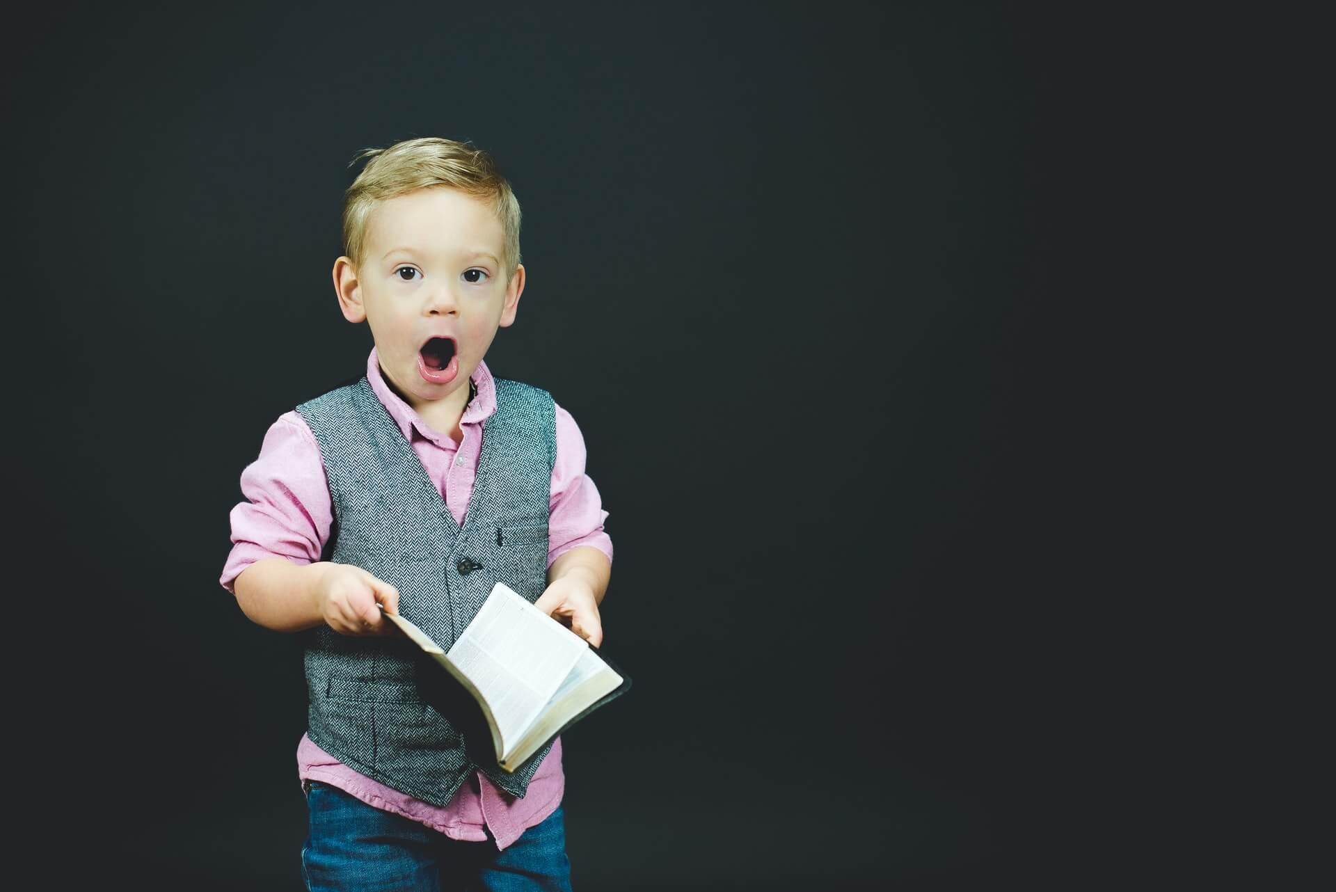 Zdziwiony chłopiec z książką w ręku.