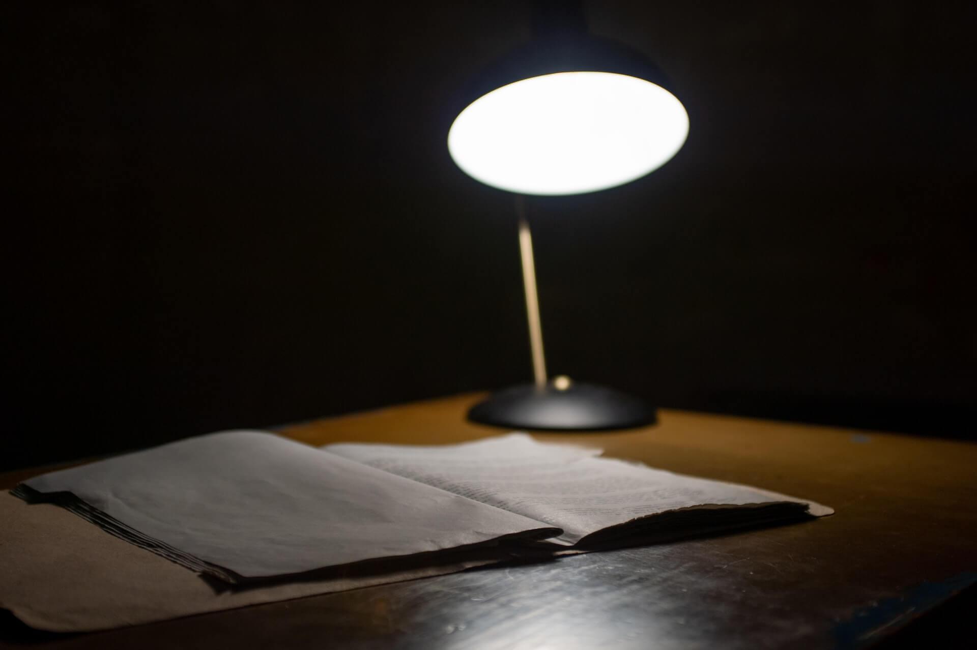 Lampa na stole, oświetlająca dokumenty.
