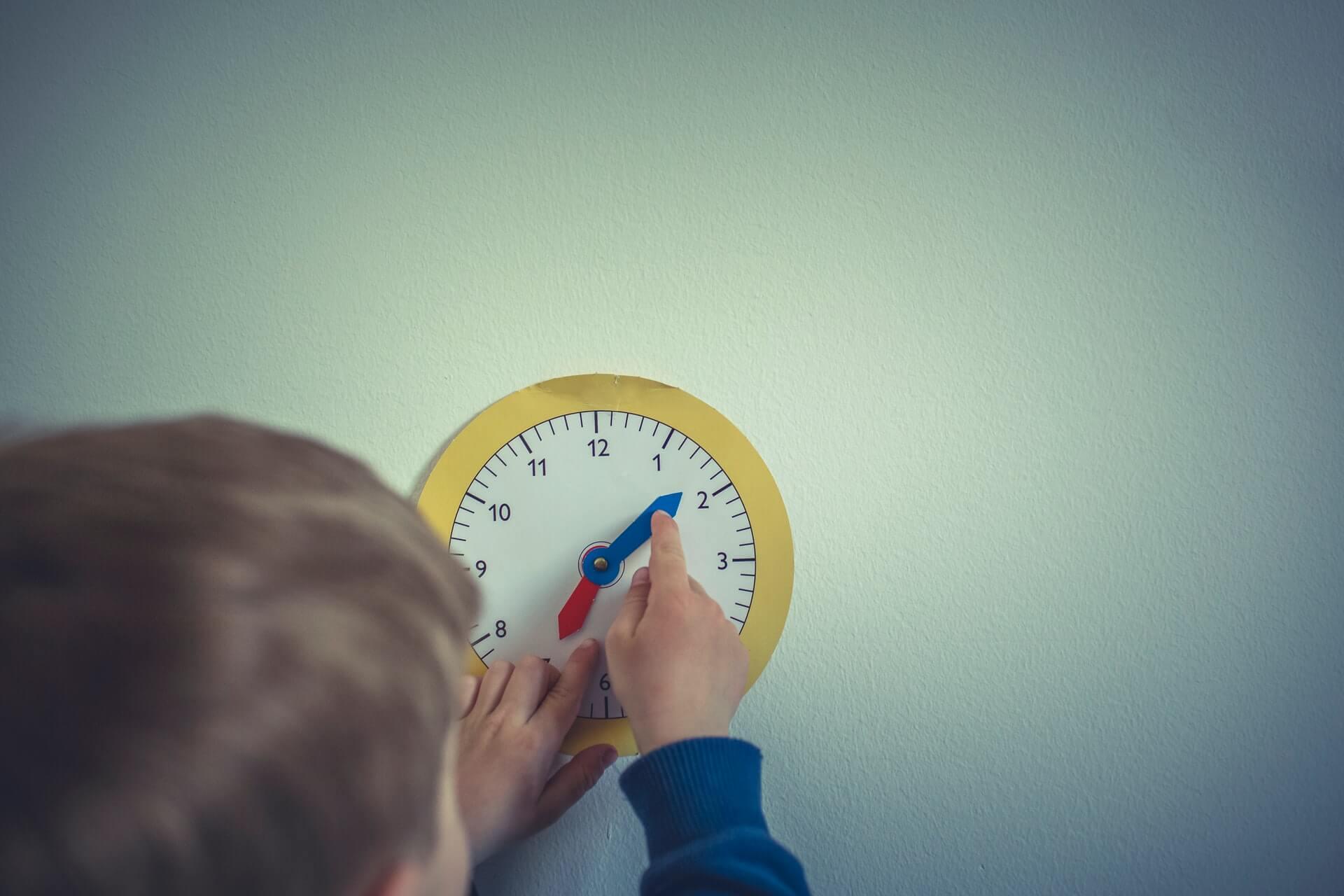 Dziecko nastawiające wskazówki namalowanego zegara.