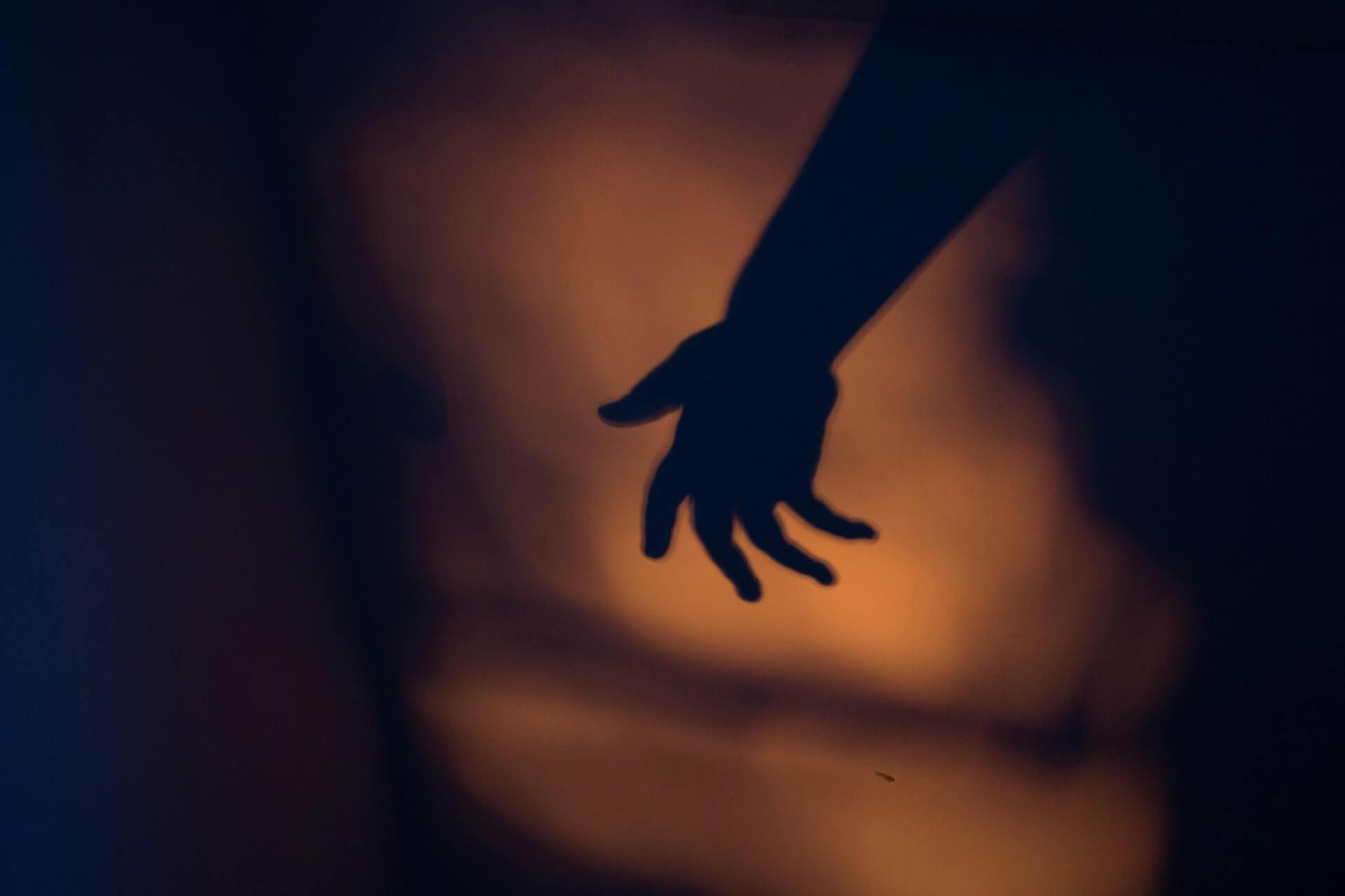 Cień ręki, na ciemnym tle.