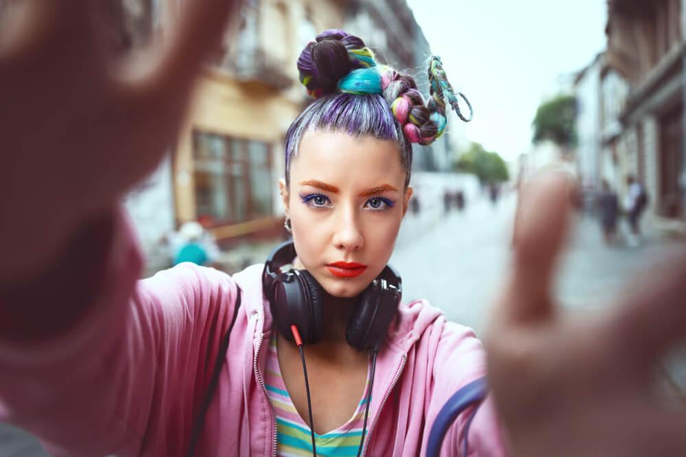 Dziewczyna w kolorowych włosach, ustawiająca ręce tak, jakby chciała ustawić aparat, aby zrobić sobie selfie.