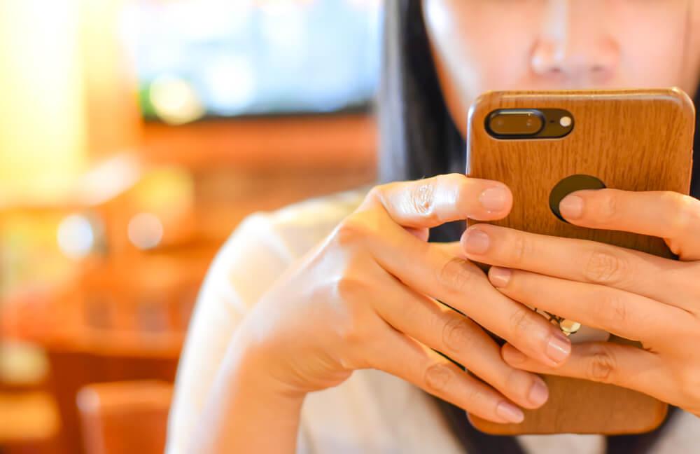 Dziewczyna trzymająca telefon w rękach.