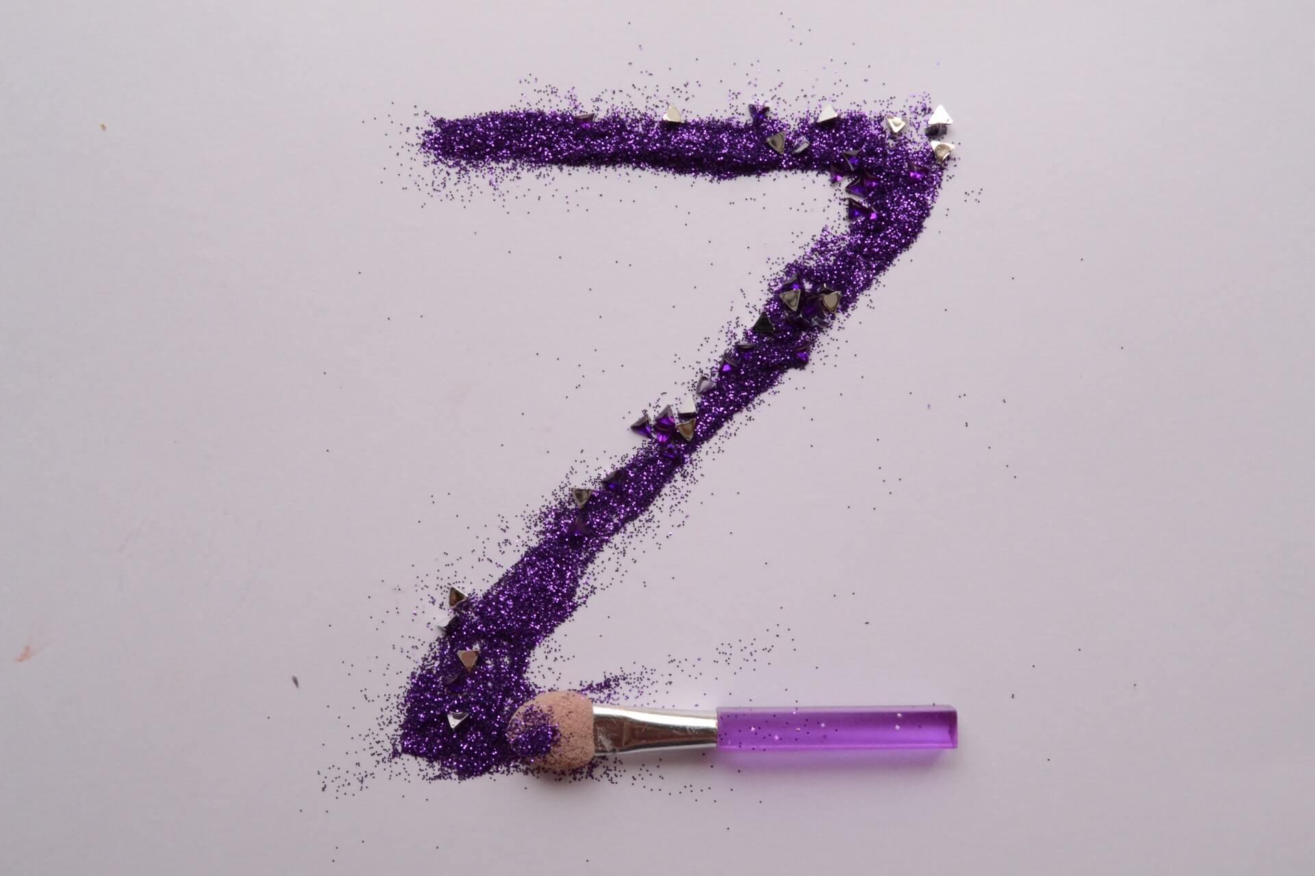 """Wielkie, fioletowe """"Z"""" napisane cieniem do powiek. Na dole litery znajduje się pacynka do makijażu. Wszystko na tle w kolorze przybrudzonego różu."""