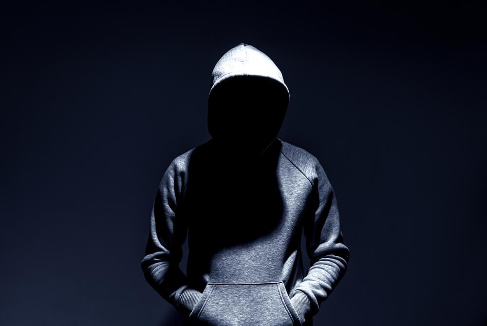 Czarne tło i postać w szarej bluzie z kapturem. Nie widać twarzy, jest przykryta czarnym cieniem.