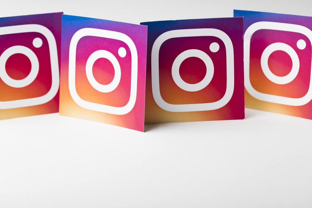 Kartki z logo Instagrama, poustawiane są obok siebie w rzędzie. Na białym tle.